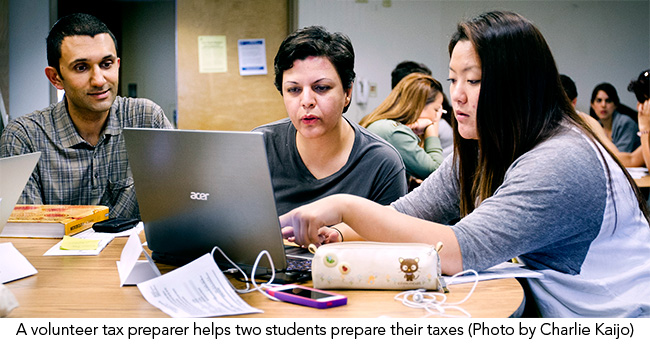 A volunteer tax preparer helps two students prepare their taxes.