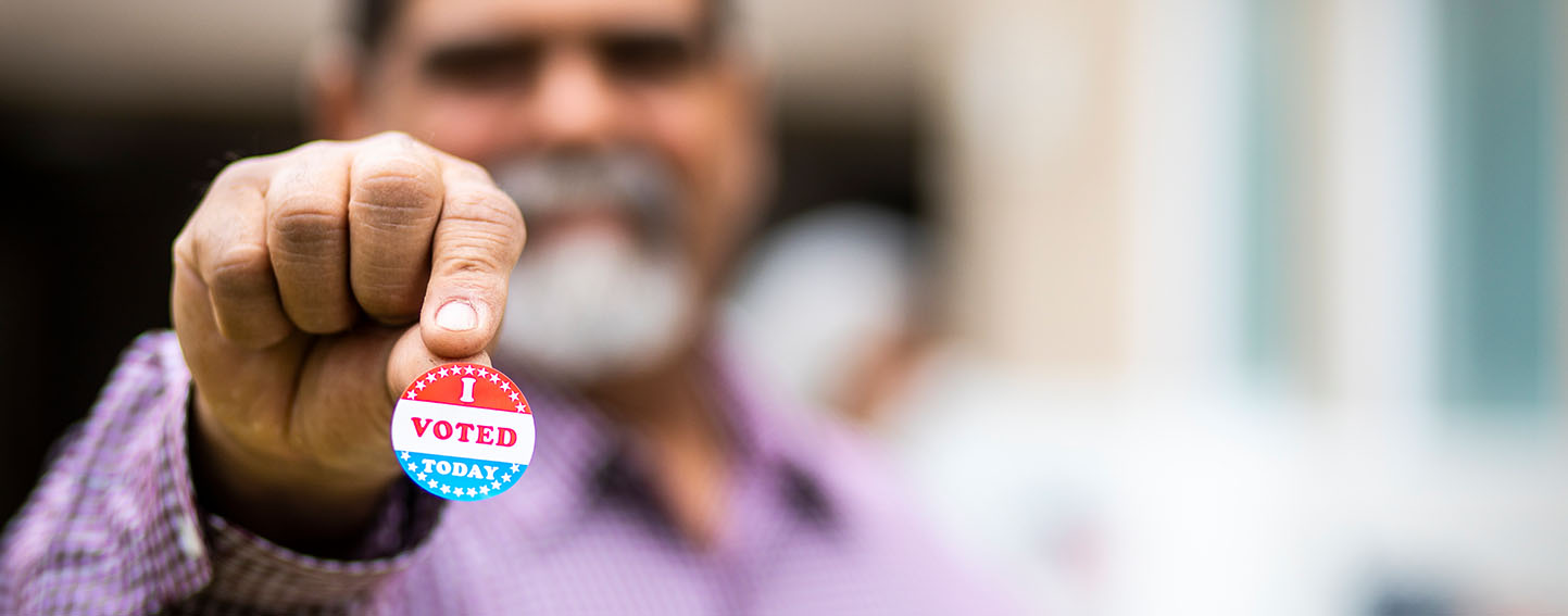 """Man holding his """"I Voted"""" sticker"""