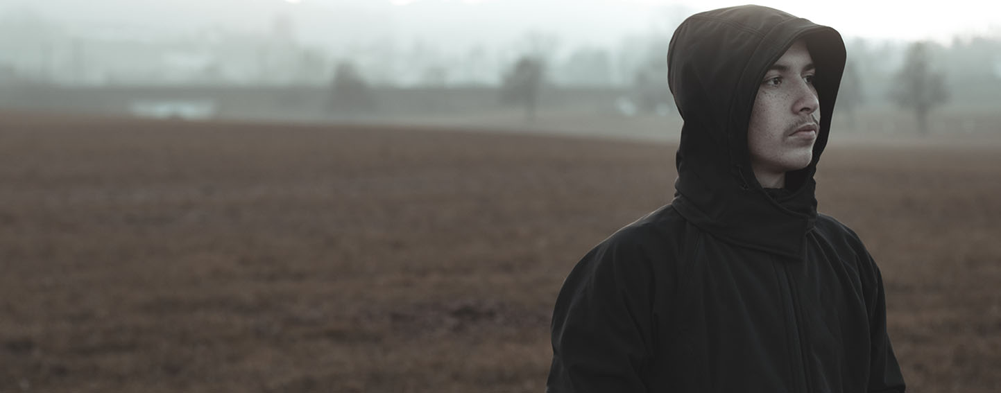 Pensive young man stands alone on a foggy field.
