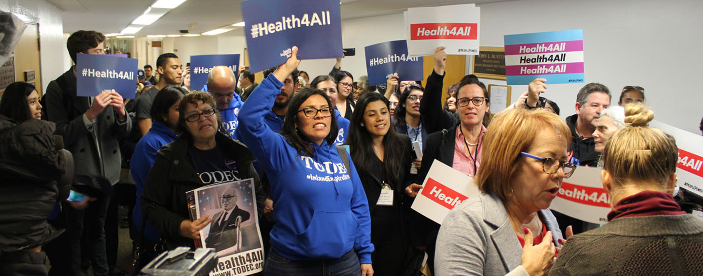 A crowd gathers around state Sen. Maria Elena Durazo before a committee hearing on legislation that would expand Medicaid coverage to adults who are in the country illegally. (Harriet Blair Rowan/California Healthline)