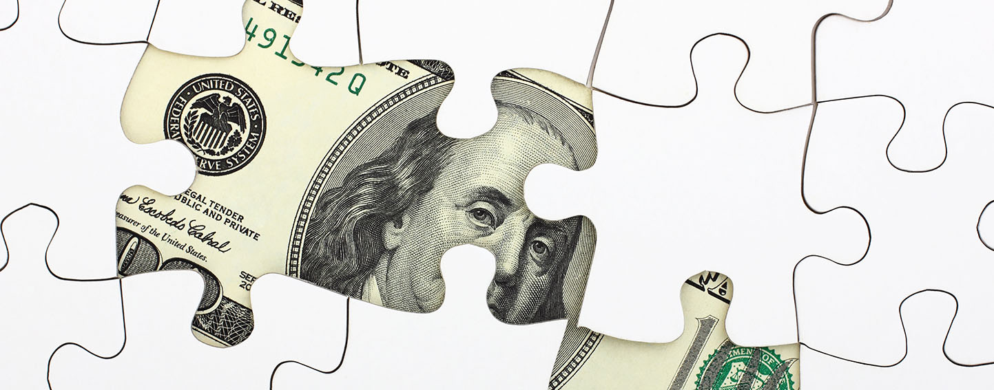 Benjamin Franklin's portrair on a one hundred dollar bill peeks out from underneath a puzzle