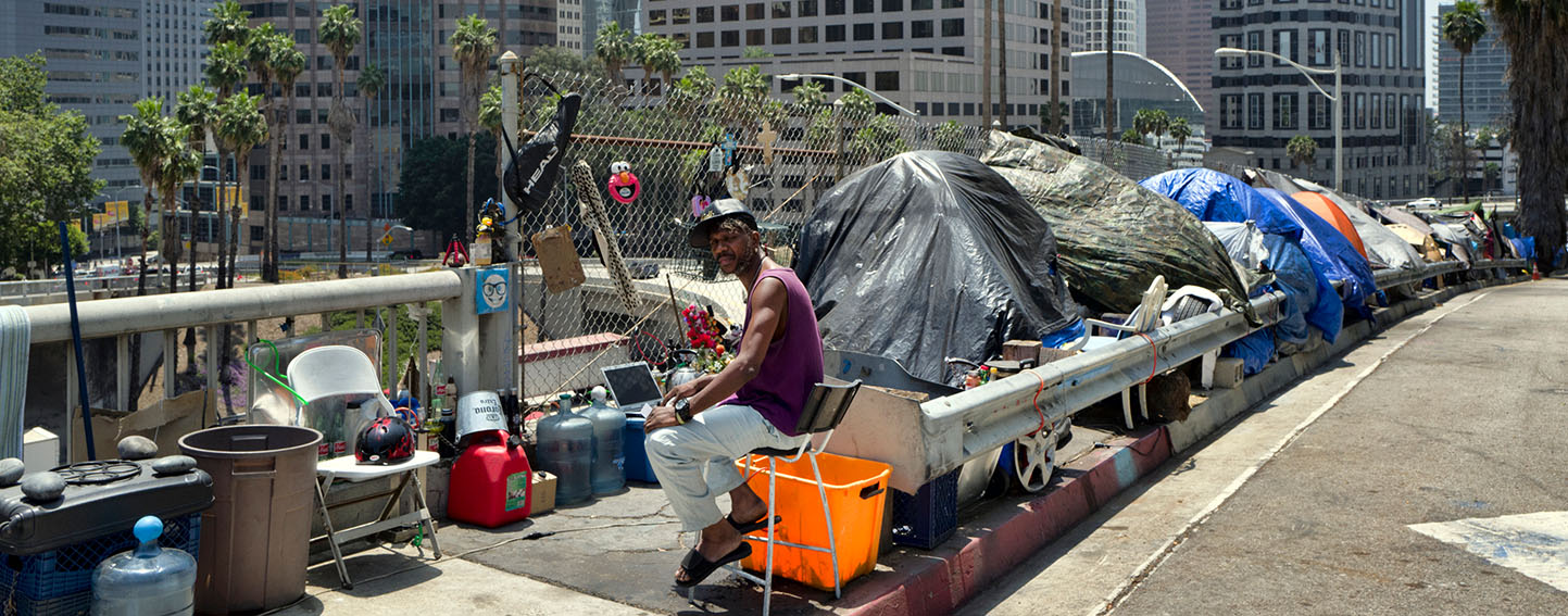 A man sits at his tent in a homeless encampment, along the Interstate 110 freeway in downtown Los Angeles.