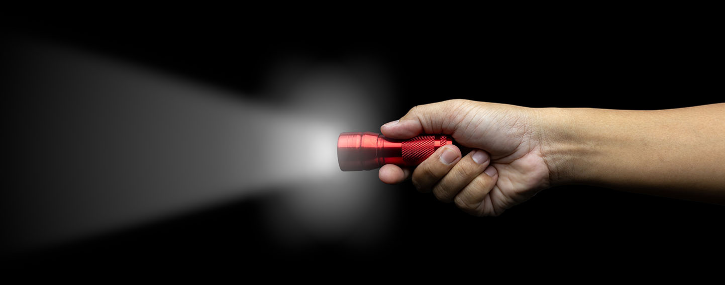 hand holding red flashlight against a black background