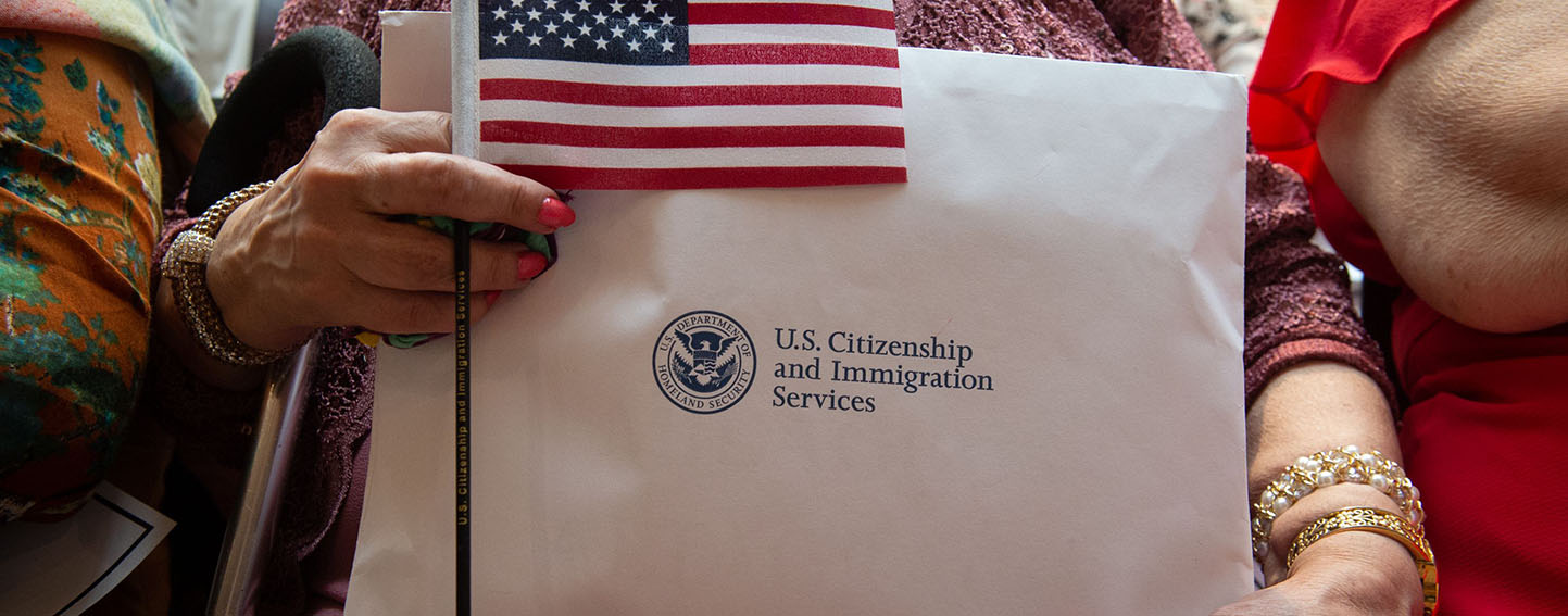 new citizen holds citizenship documents and a flag