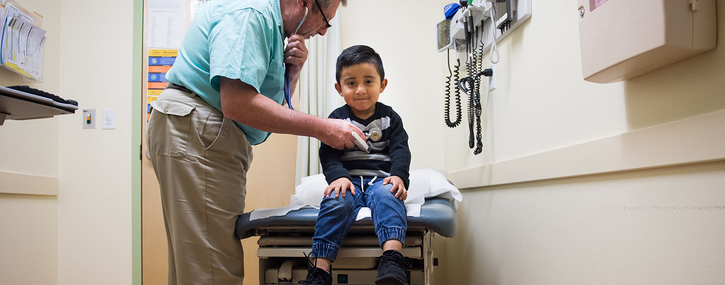 Young client is seen by medical practitioner at La Clinica, Oakland, CA.