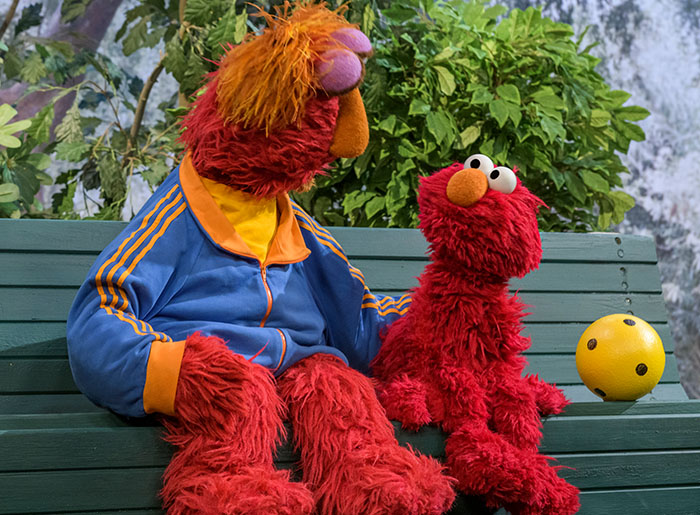 Sesame Street character Elmo sits with his father on a park bench.