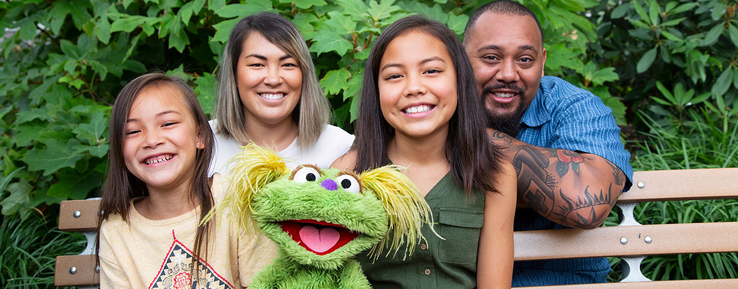 Sesame Street character, Karli, and family sit on bench.