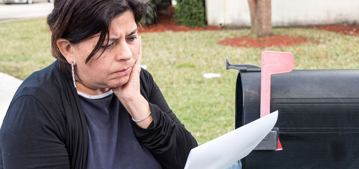 concerned woman reading mail at mailbox