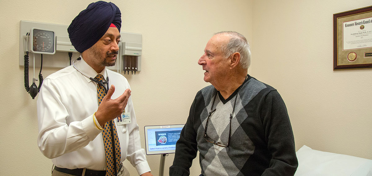 Prabhdeep Singh, MD, talks to patient in exam room