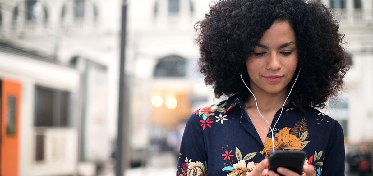 young woman listening to her phone through headphones