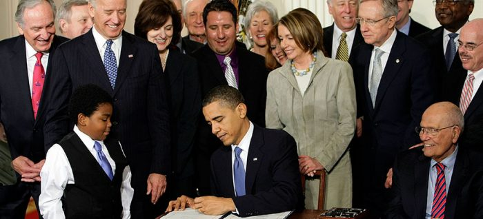 President Obama signing the Affordable Care Act in front of a crowd of legislators and citizens.