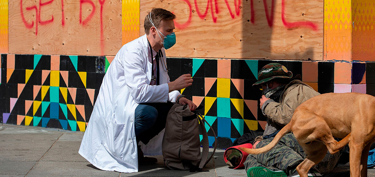 a doctor with the Haight Ashbury Free Clinic, speaks with person experiencing homelessness about the coronavirus