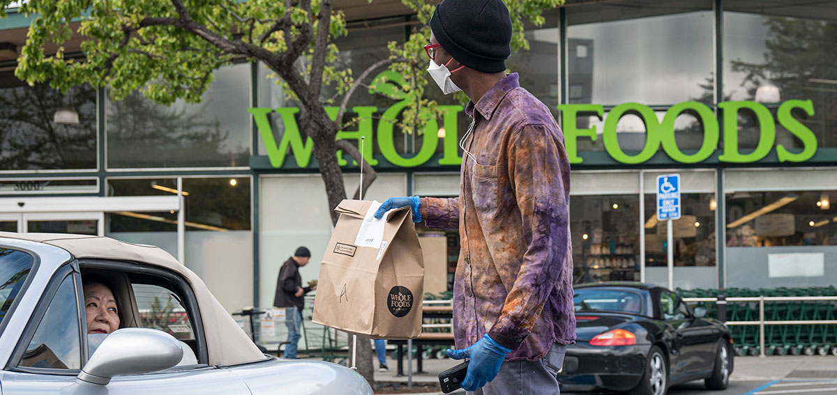 An employee wearing a protective mask hands a shopping bag to a customer outside a Whole Foods Market.