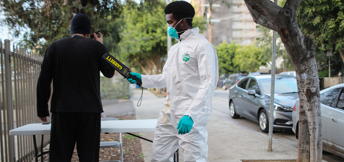 Security worker wearing mask, glove, and coveralls during COVID-19 outbreak.