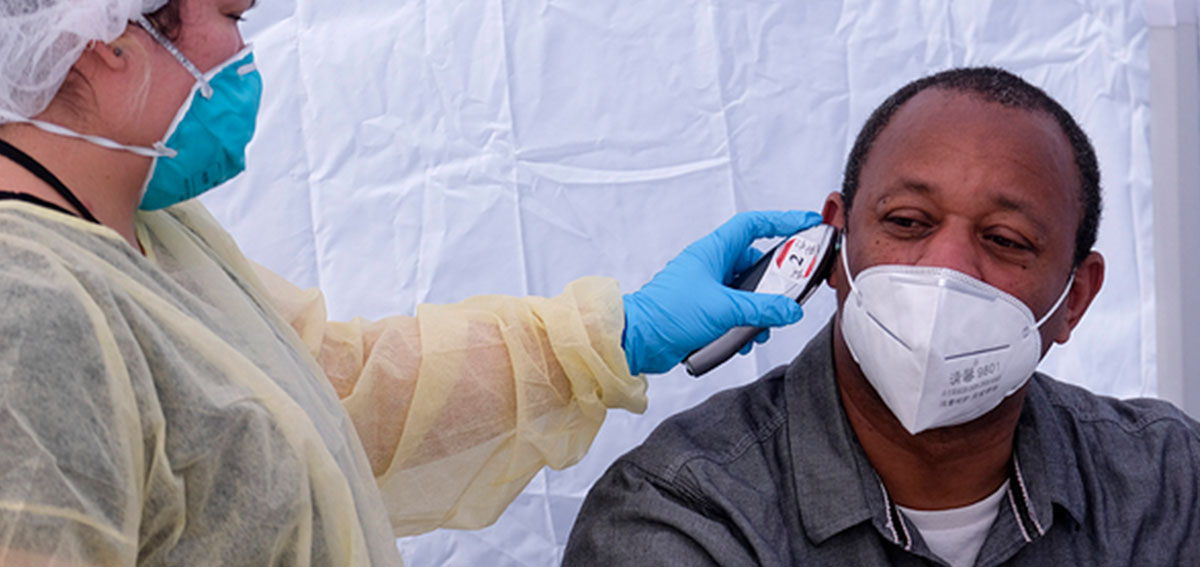Man having his temperature taken at a COVID-19 Testing Site