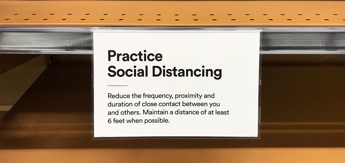 Sign on grocery store shelf reminding customers to practice social distancing