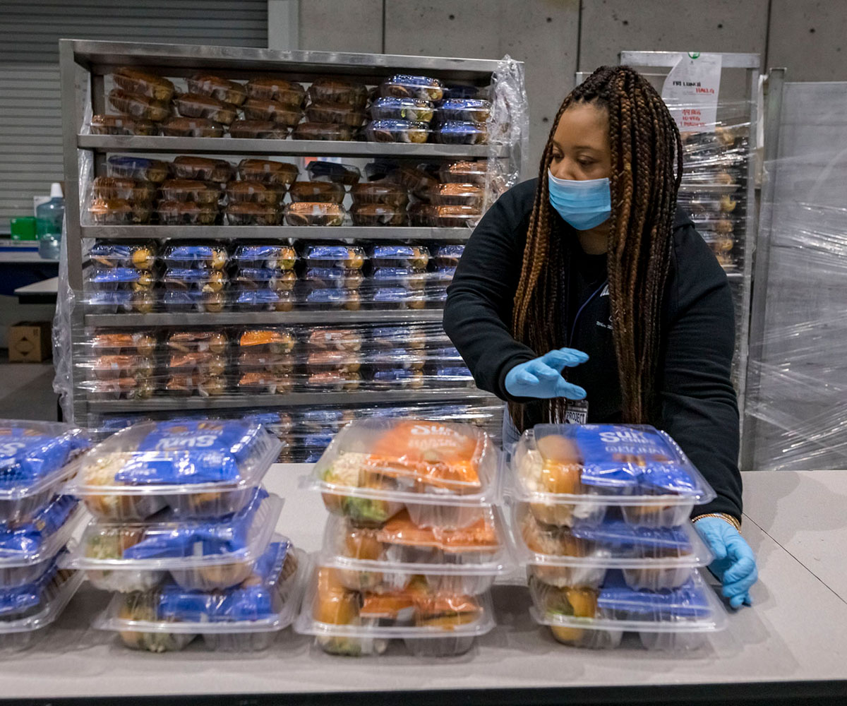 lpha Project employee Danielle Cason puts prepared meals out for the SDCC residents.