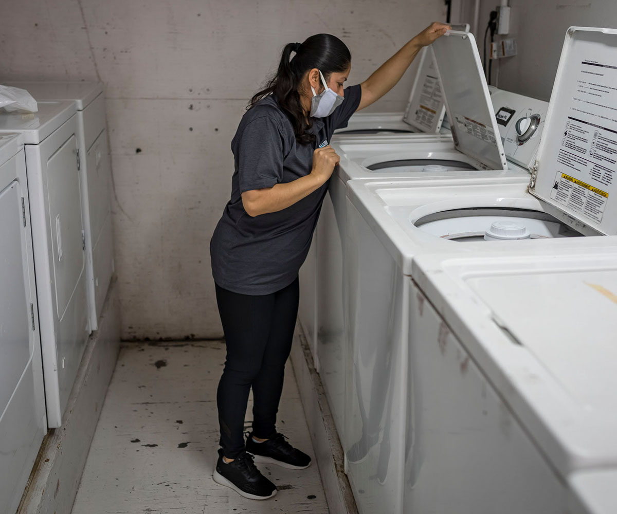 Margarita Sandoval, an employee of Allied Universal Janitorial, does residents' laundry in a trailer at Operation Shelter to Home.