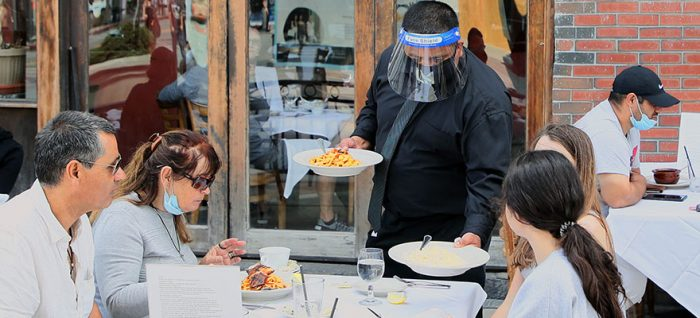 Waiter serves meal to customers wearing PPE
