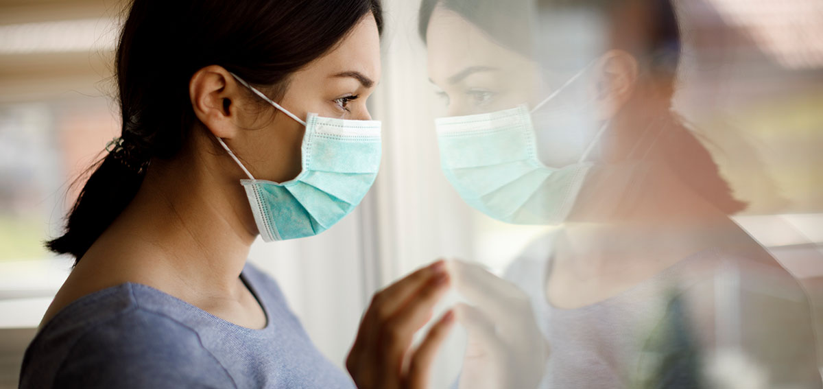 woman wearing surgical mask looking out of window
