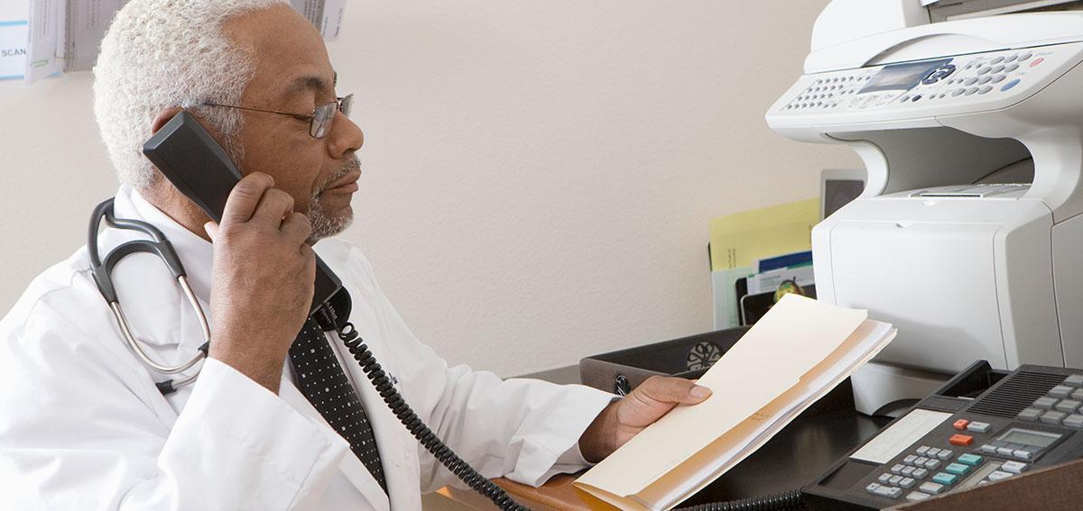 Doctor speaking on phone, holding file folder.