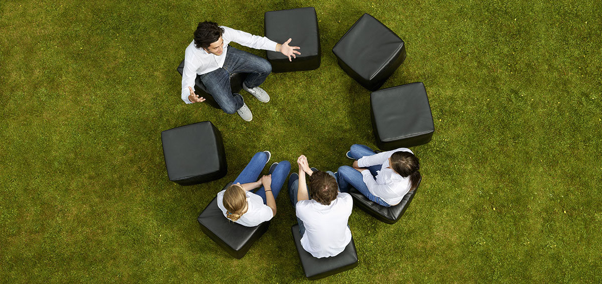four people sit in a circle on a green lawn having an animated conversation