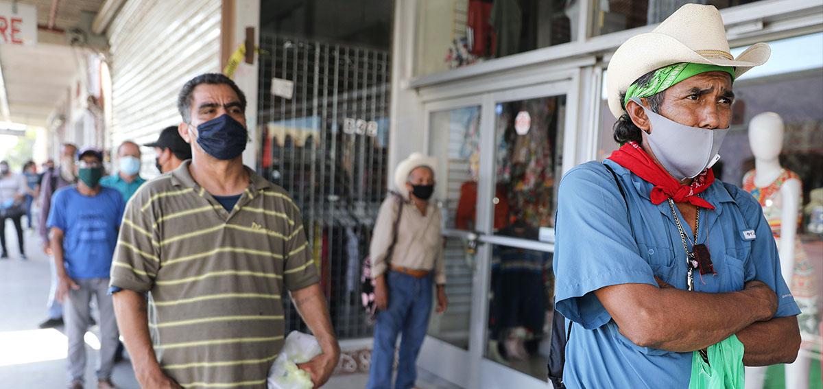 men waiting in line wearing cloth masks