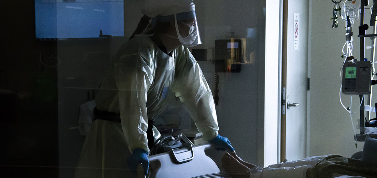 A nurse wearing a powered air-purifying respirator checks on a patients vital signs inside a Covid-19 intensive care unit.