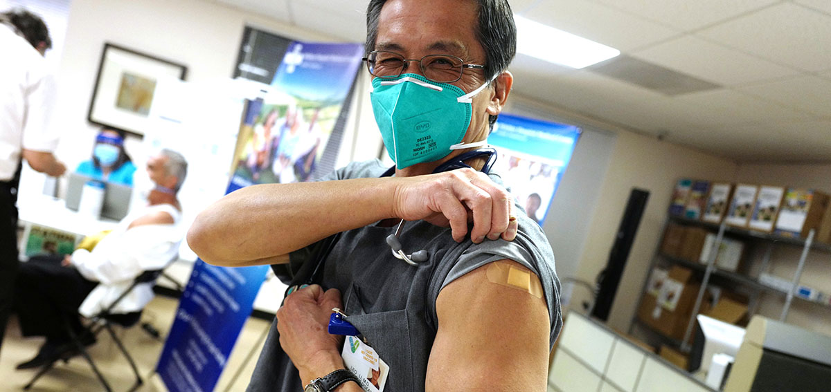 Doctor shows COVID-19 Vaccination on his arm.