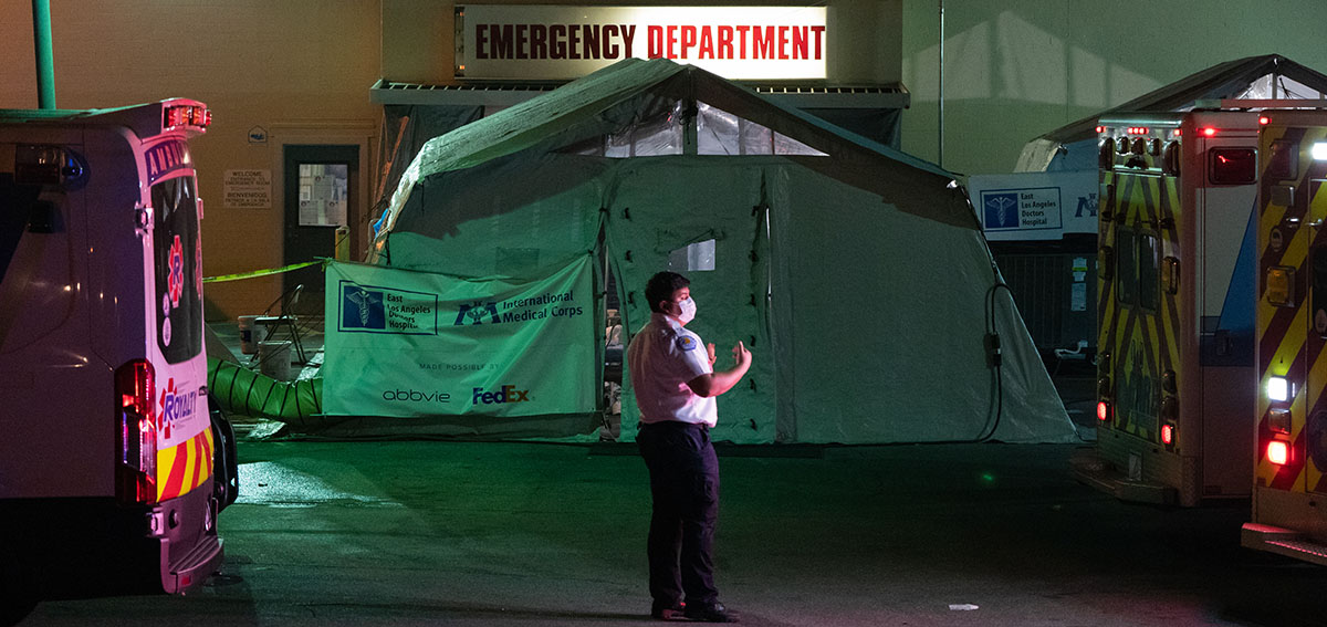 An emergency medical technician (EMT) directs an ambulance outside the emergency room