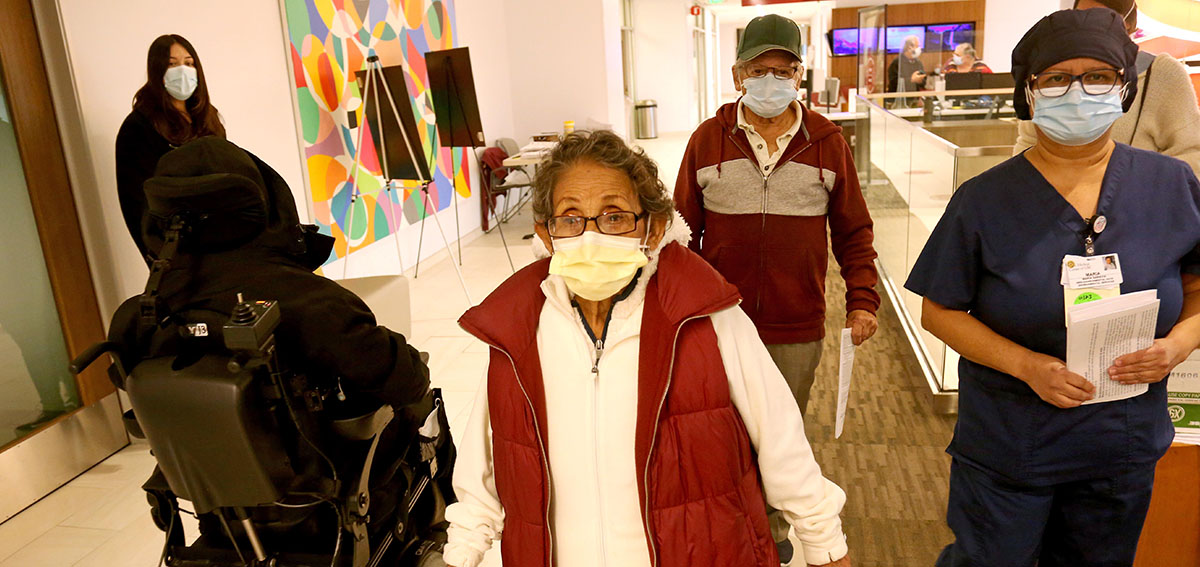 Maria Saravia, right, an Environmental Services Worker at Keck Hospital of USC, walks with her parents Sara, 81, and Juan Saravia, 83, where Marias parents will receive the vaccine against COVID-19