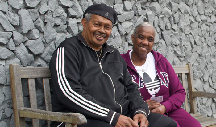 Rev. Johnnie Clark and Gloria Clark sit on a bench together.