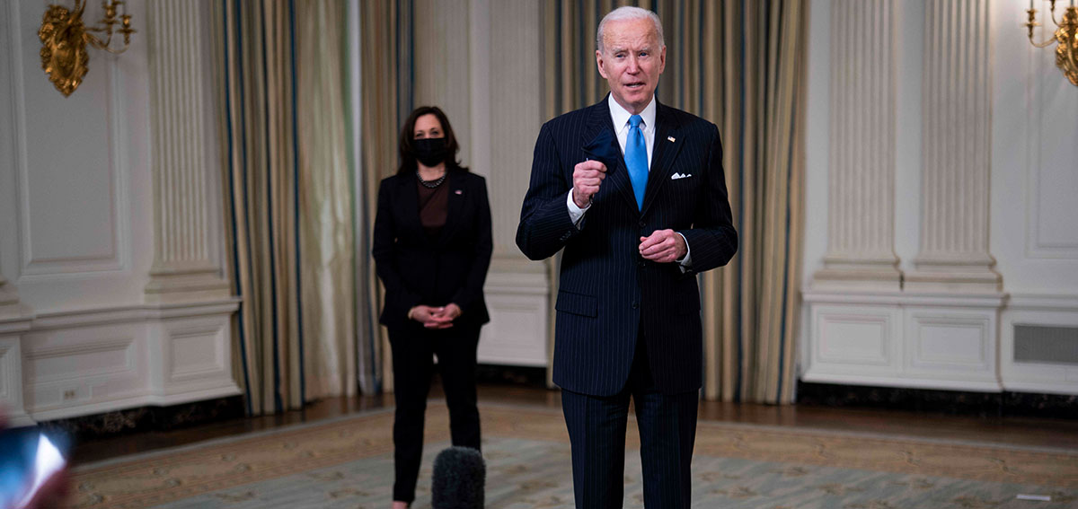 United States President Joe Biden listens to a reporter's question. US Vice President Kamala Harris stands in the background.