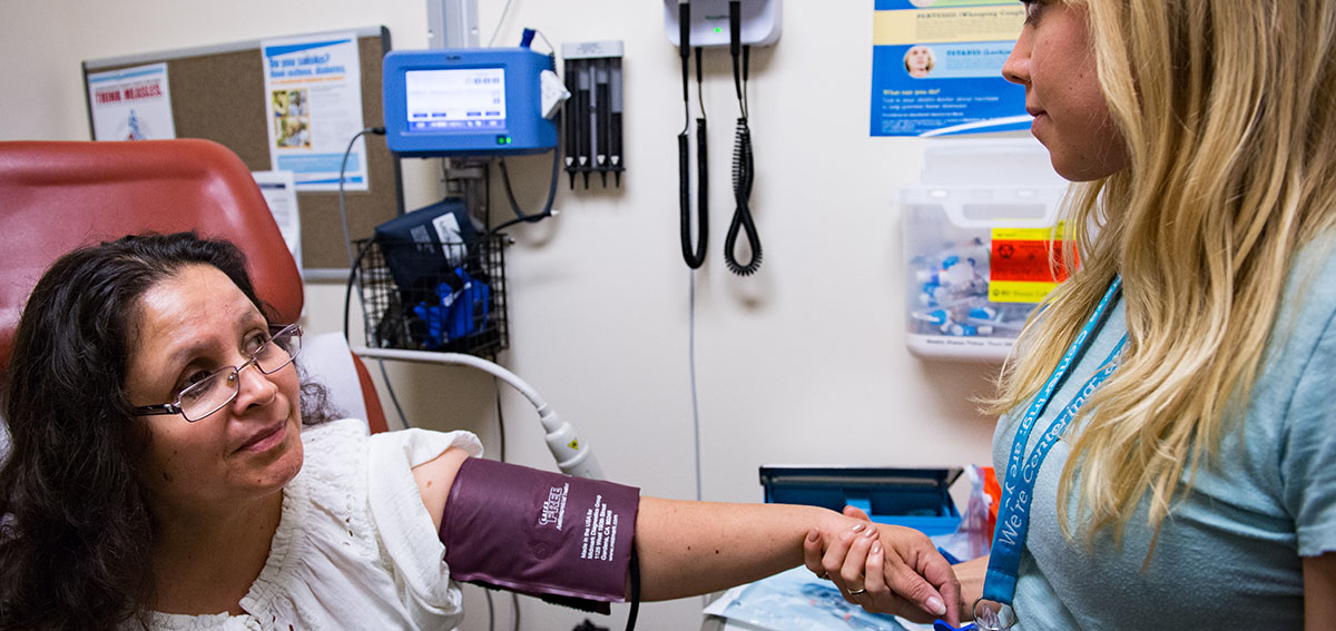 Woman receives a blood pressure check at clinic