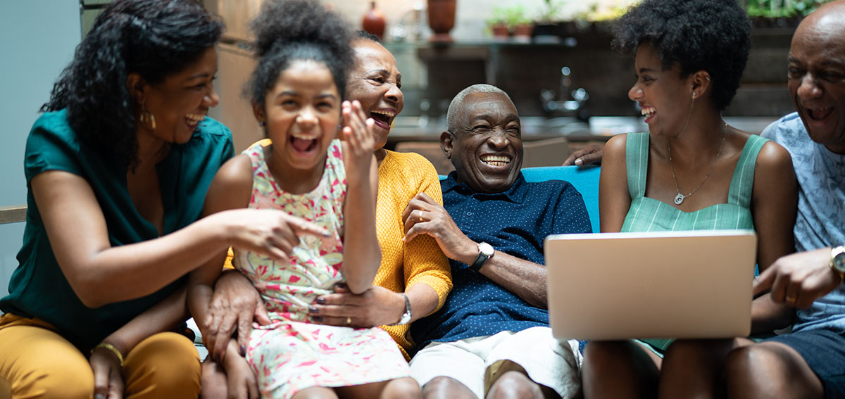 Black family sitting on couch together, looking at something on a laptop, laughing