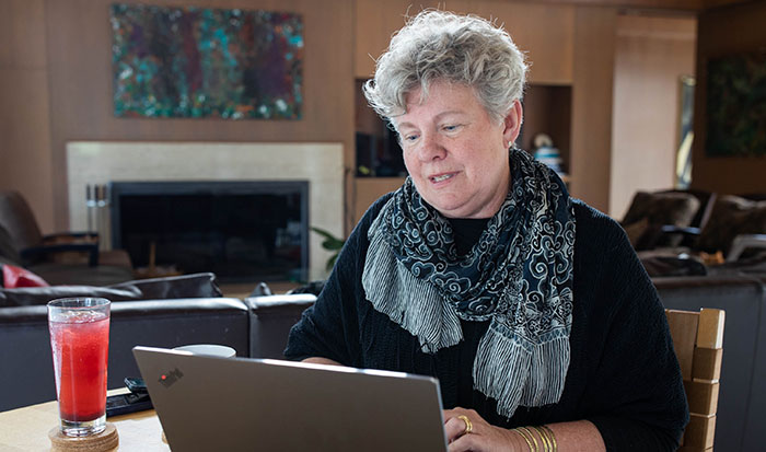 Santa Cruz County Health Officer Dr. Gail Newel sitting at a table, working on a laptop.