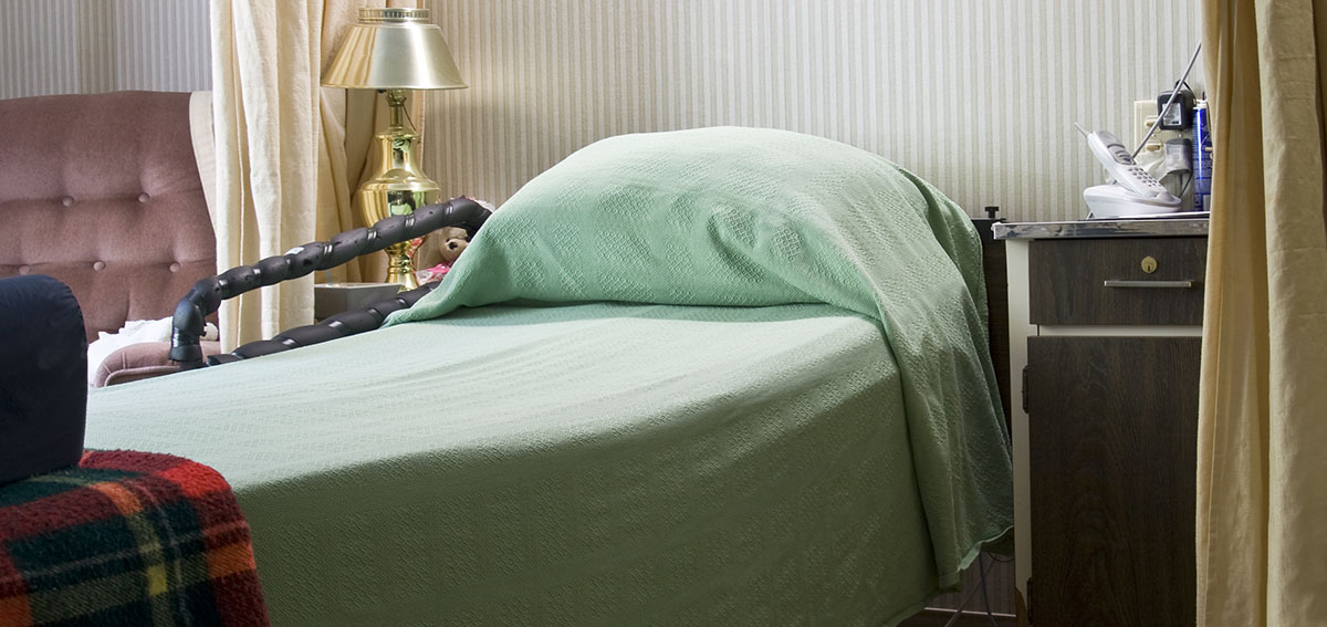 A bed is shown in a room at a nursing home