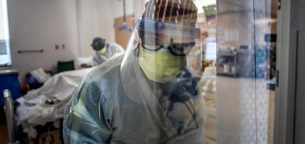 A nurse wearing personal protective equipment (PPE) speaks to a colleagues from inside an Intensive Care Unit (ICU)