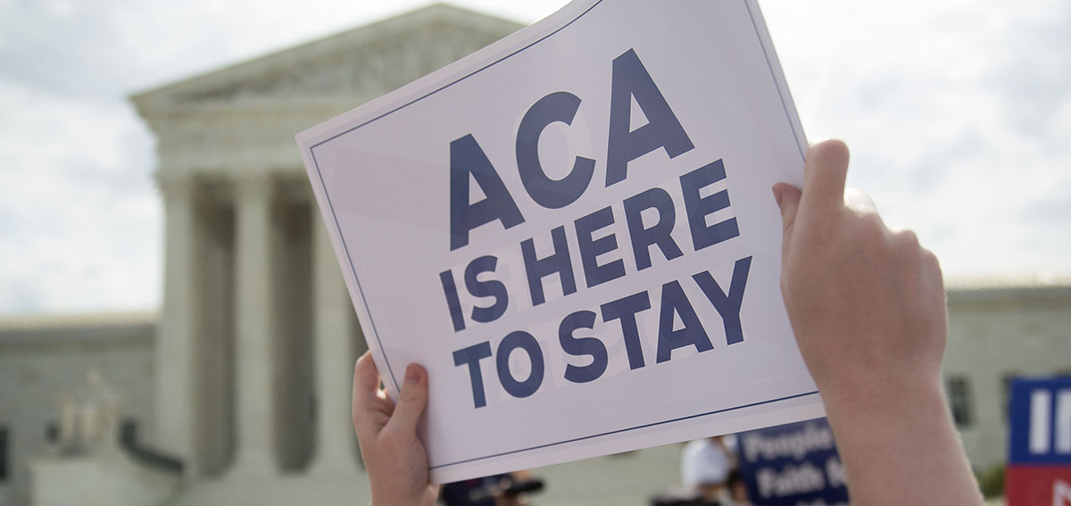 """Protestor holds sign that says """"ACA is Here to Stay"""" in front of Supreme Court building"""