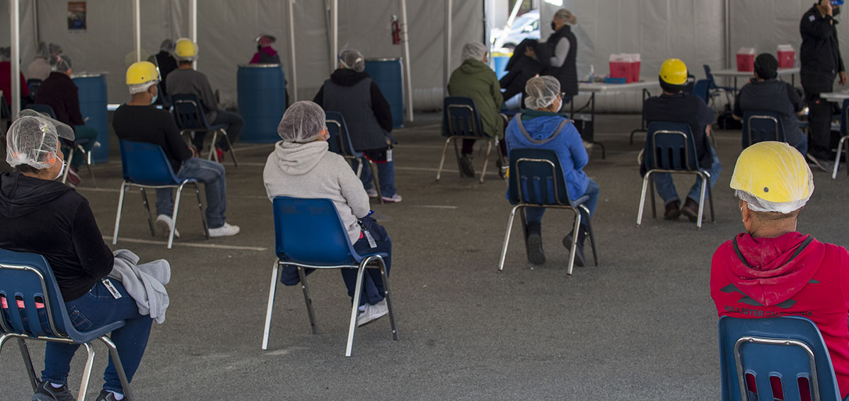 Farmworkers wait after receiving a dose of the Moderna Covid-19 vaccine at a vaccination clinic