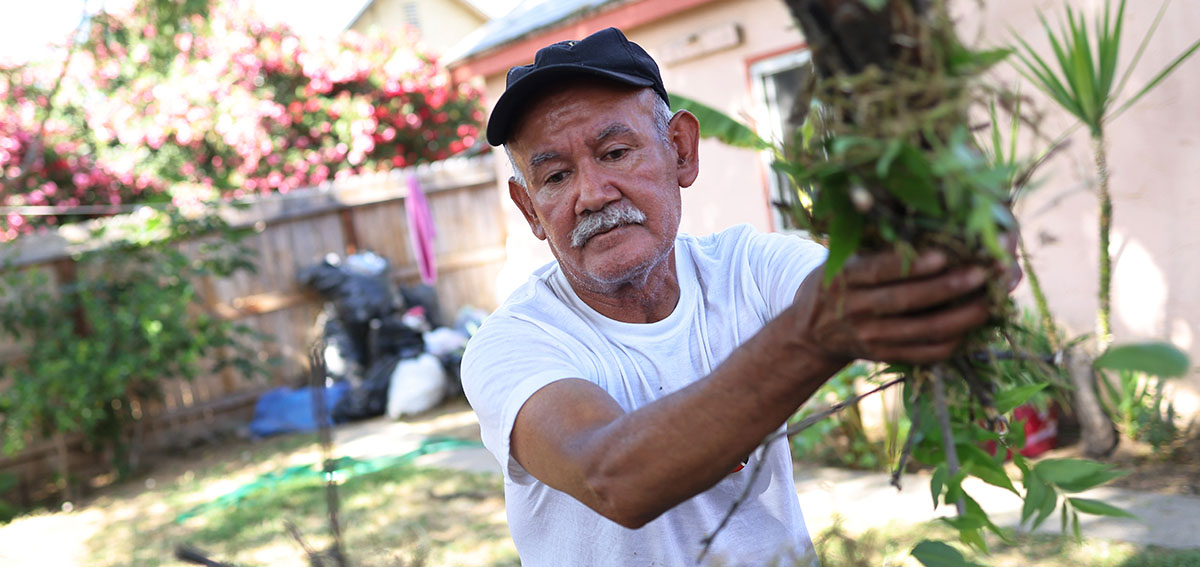 suncion Ponce, a farm worker originally from Puebla, Mexico, cleans up his yard on May 17, 2021 in Fresno, California.