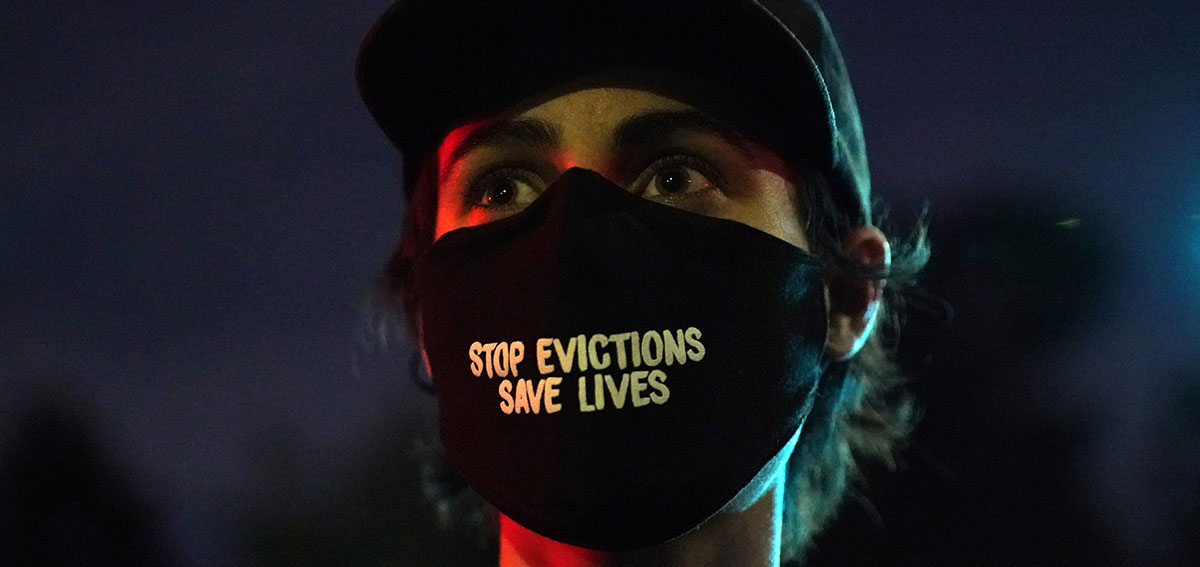 """Woman wearing mask that reads """"Stop Evictions, Save Lives"""""""