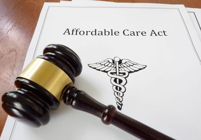 Paper copy of the Affordable Care Act with a gavel laying on top of it.
