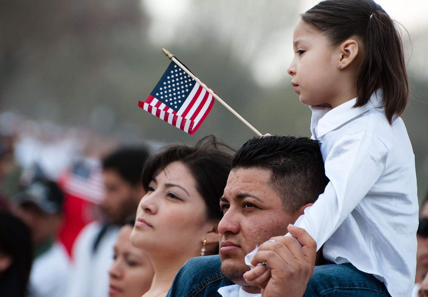 Latino family at a parade, child holding an American flag