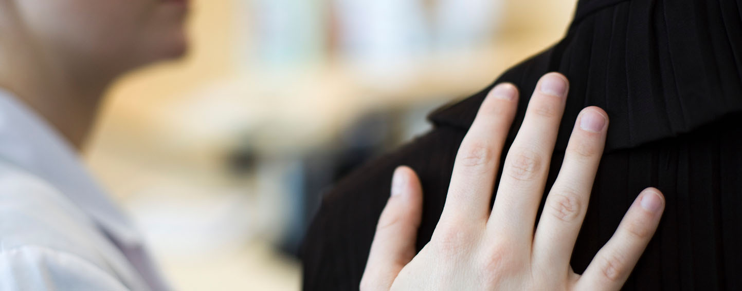 Person placing hand on another person's shoulder in a comforting gesture
