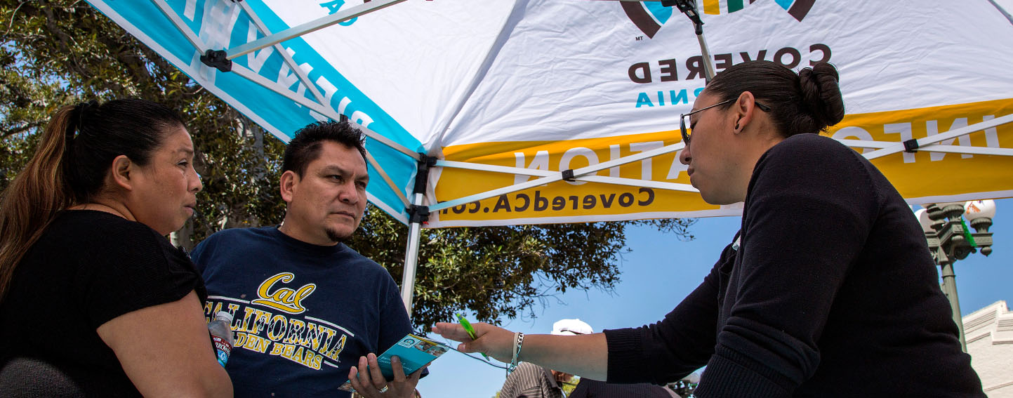 Ana Oliva, left, and Felix Portillo of Los Angeles get insurance information from Valeria Lopez at a Covered California event. Ricardo DeAratanha / Los Angeles Times