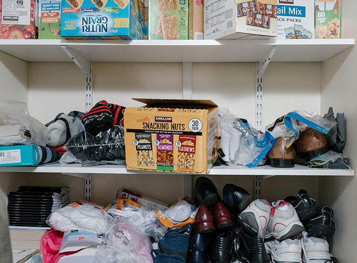 Supply closet filled with new cloting items, shoes, food and more.