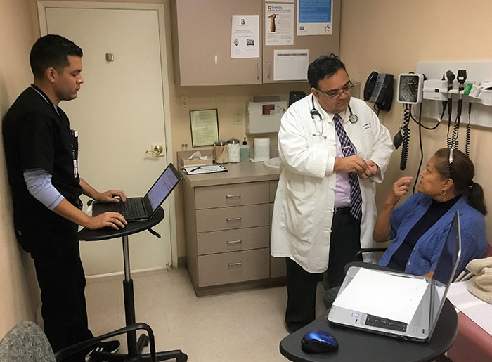 Doctor and assistant meet with patient in exam room.