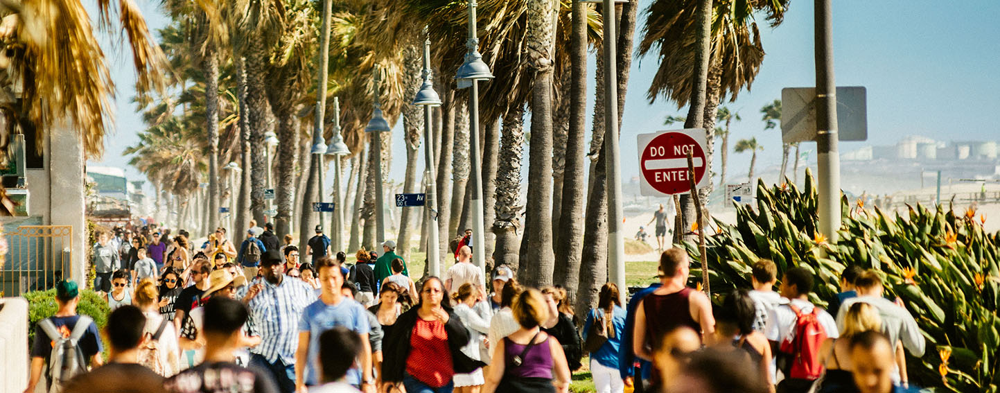 Crowd of people walking along beach path in Southern California.