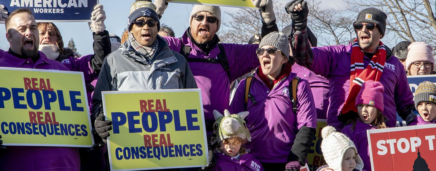 Demonstrators holding signs protesting 2019 government shutdown.